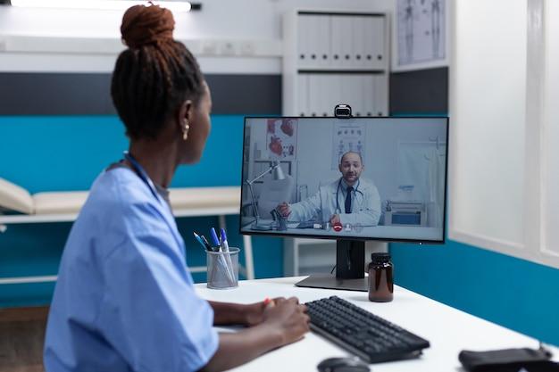 Afroamerikanische krankenschwester, die einem entfernten arzt krankheitssymptome erklärt