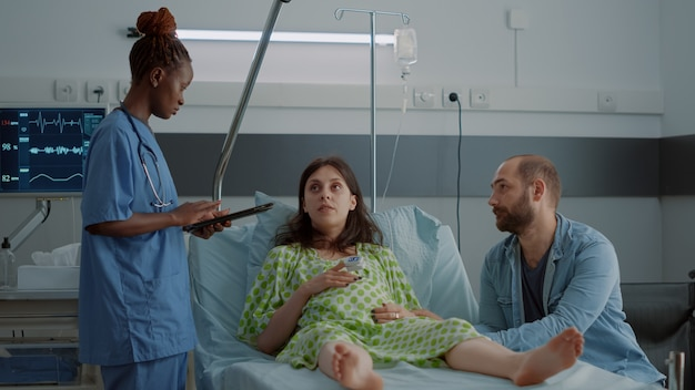 Afroamerikanische krankenschwester, die schwangere frau unterstützt