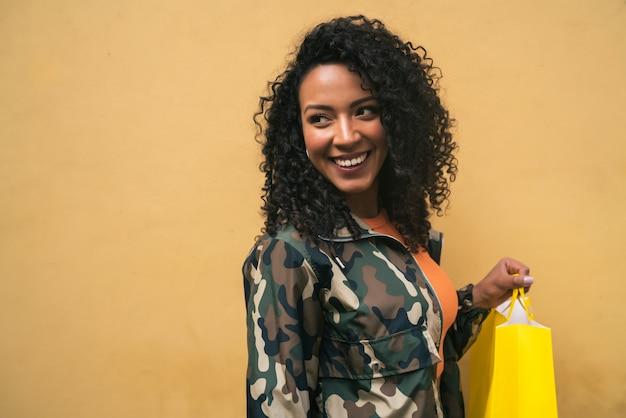 Afroamerikanische lateinische frau, die einkaufstaschen hält.