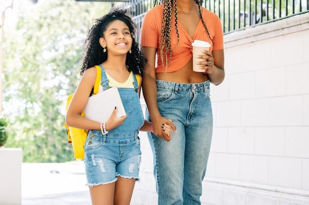 Afroamerikanische mutter, die ihre tochter zur schule bringt. bildungskonzept.
