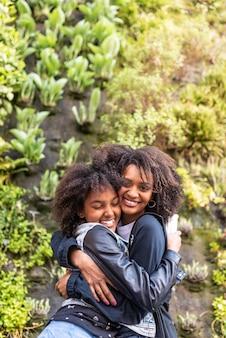 Afroamerikanische mutter und tochter, die sich umarmen.