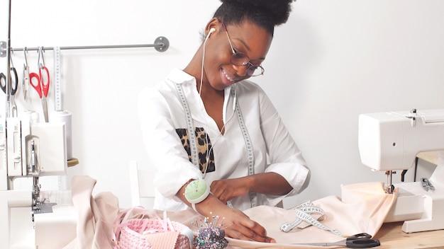 Afroamerikanische näherin, modedesignerin, die musik über kopfhörer hört, während sie in der studio-werkstatt an stoff arbeitet