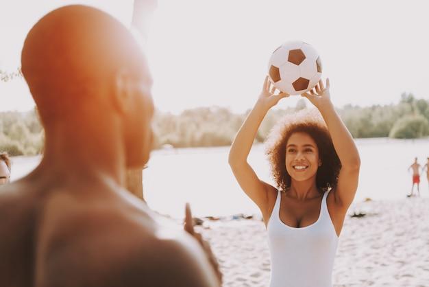 Afroamerikanische paare, die ball auf strand spielen