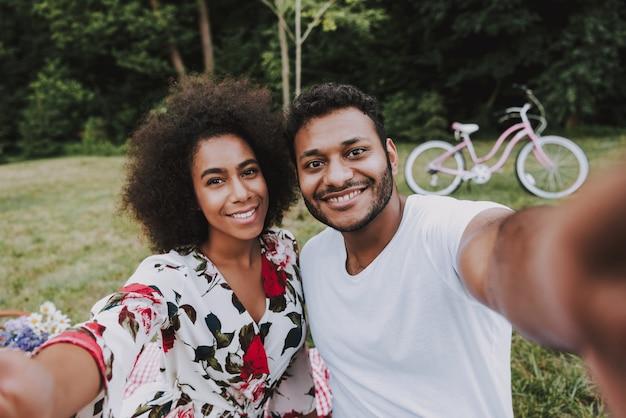 Afroamerikanische paare, die selfie auf einem picknick tun