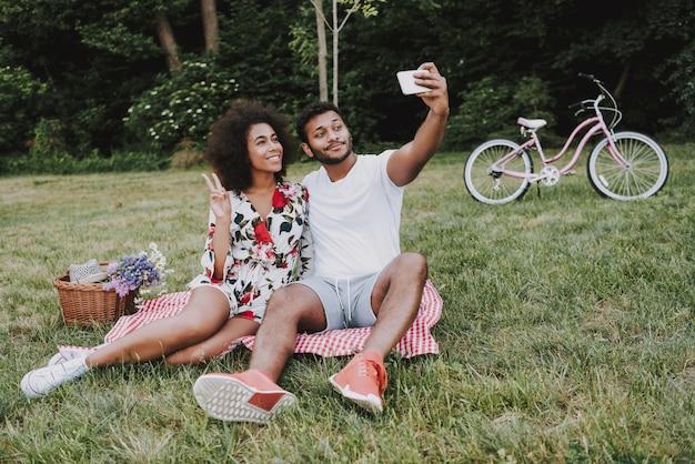 Afroamerikanische paare, die zusammen selfie auf einem picknick tun