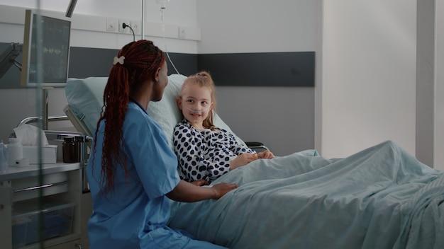 Afroamerikanische praktizierende krankenschwester, die mit kleinem patienten über krankheitsbehandlung diskutiert