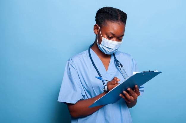 Afroamerikanische therapeutenkrankenschwester, die eine schützende medizinische gesichtsmaske gegen coronavirus trägt
