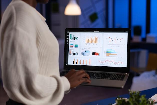 Afroamerikanische unternehmerin, die finanzdiagramme analysiert