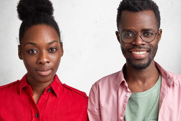 Afroamerikanische weibliche und männliche klassenkameraden treffen sich nach langer zeit, tauschen nachrichten aus und stehen nahe beieinander.