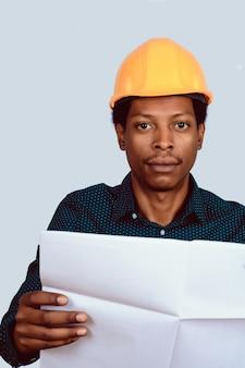 Afroamerikanischer architekt im schutzhelm mit lichtpause.