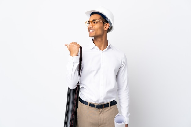 Afroamerikanischer architekt mann mit helm und blaupausen über isoliertem weißem hintergrund _ zeigt zur seite, um ein produkt zu präsentieren