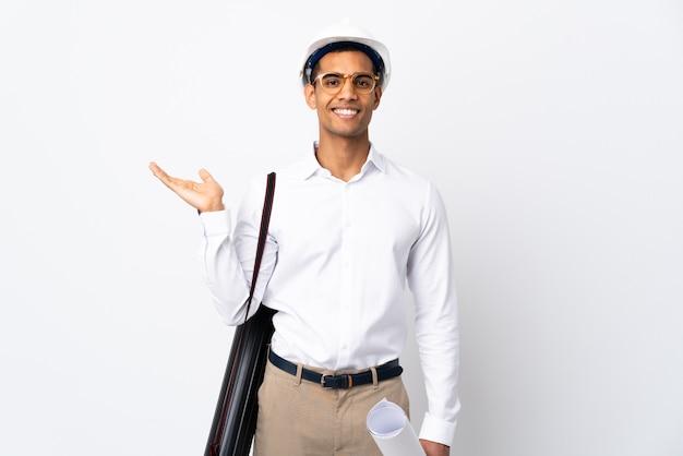 Afroamerikanischer architekt mann mit helm und blaupausen über isolierter weißer wand _ hält imaginären copyspace auf der handfläche, um eine anzeige einzufügen
