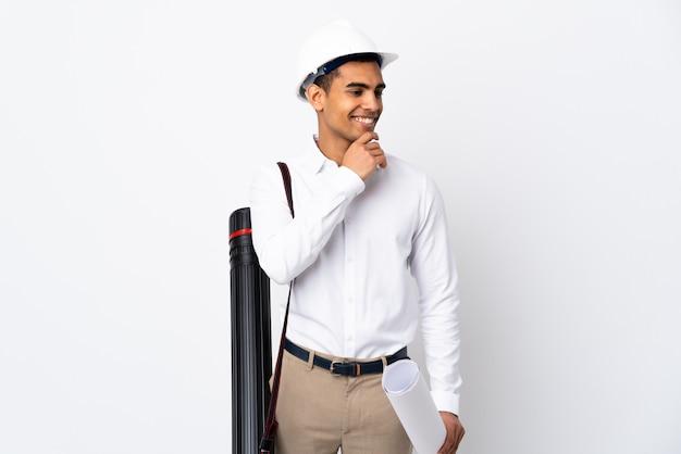 Afroamerikanischer architekt mann mit helm und hält blaupausen über isolierte weiße wand, die zur seite schaut und lächelt