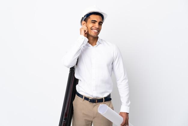 Afroamerikanischer architekt mann mit helm und hält blaupausen über isolierte weiße wand _ lachen
