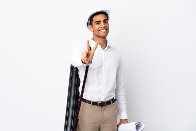 Afroamerikanischer architekt mann mit helm und hält blaupausen über isolierte weiße wand _ lächelnd und siegeszeichen zeigend