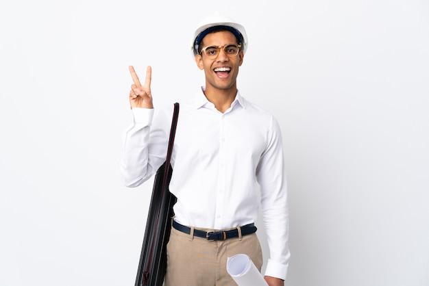 Afroamerikanischer architekt mann mit helm und hält blaupausen über isolierten weißen hintergrund _ lächelnd und siegeszeichen zeigend