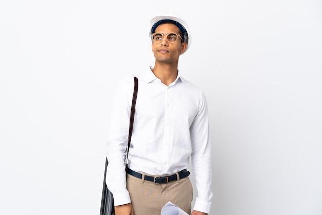 Afroamerikanischer architekt mann mit helm und hält blaupausen über isolierten weißen hintergrund _. porträt