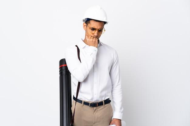 Afroamerikanischer architektenmann mit helm und blaupausen über isoliertem weißem hintergrund, der zweifel hat