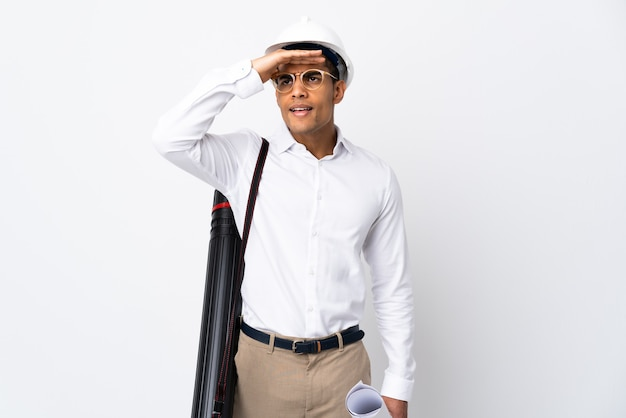 Afroamerikanischer architektenmann mit helm und blaupausen über isoliertem weißem hintergrund _ weit weg mit der hand schauend, um etwas zu schauen