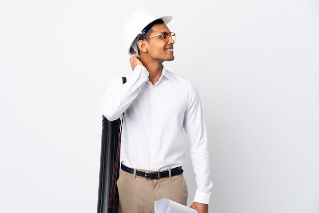 Afroamerikanischer architektenmann mit helm und blaupausen über isolierter weißer wand, die eine idee denkt