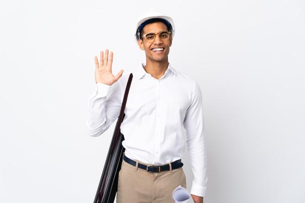 Afroamerikanischer architektenmann mit helm und blaupausen über isolierter weißer wand, die mit hand mit glücklichem ausdruck salutiert