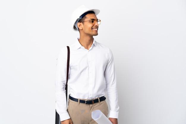 Afroamerikanischer architektenmann mit helm und blaupausen über isolierter weißer wand, die zur seite schaut und lächelt
