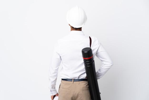 Afroamerikanischer architektenmann mit helm und blaupausen über isolierter weißer wand _ in der hinteren position