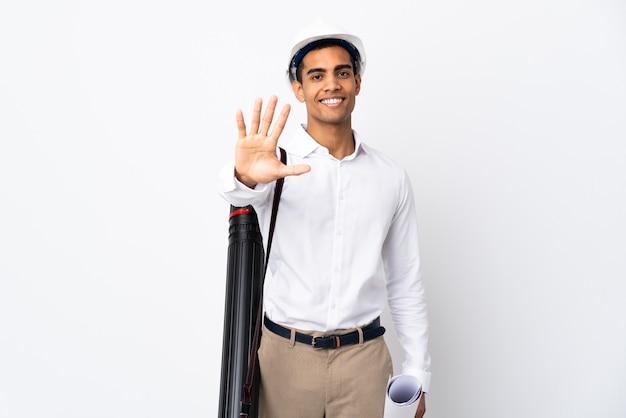 Afroamerikanischer architektenmann mit helm und blaupausen über lokalisiertem weißem hintergrund, der fünf mit den fingern zählt