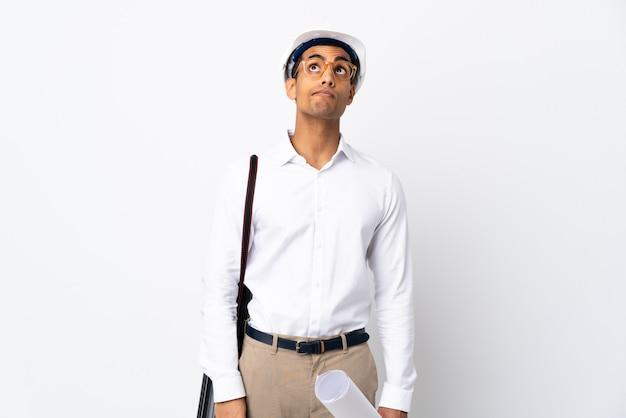 Afroamerikanischer architektenmann mit helm und hält blaupausen über isolierter weißer wand _ und schaut nach oben