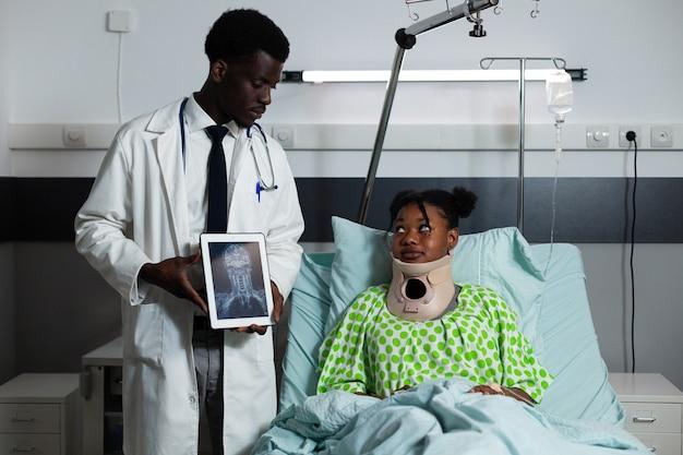 Afroamerikanischer arzt, der dem patienten röntgentablette zeigt