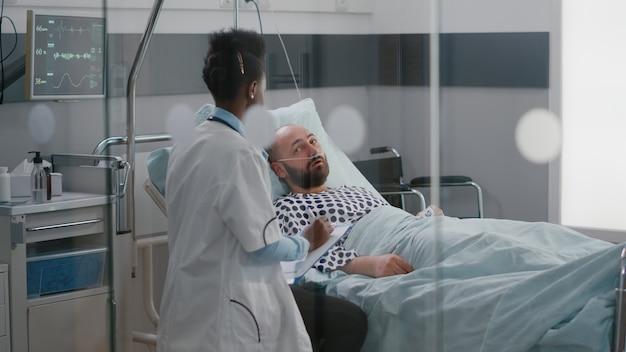Afroamerikanischer arzt, der den kranken mann überprüft, der krankheitssymptome überwacht