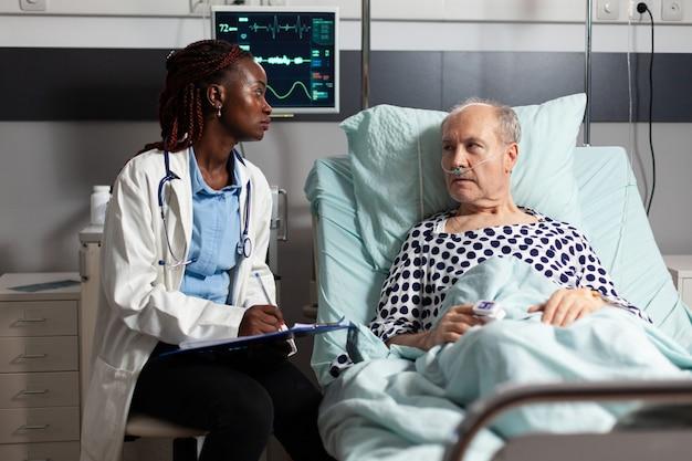 Afroamerikanischer arzt, der die diagnose von der zwischenablage zu einem kranken, unwohlen älteren patienten liest, der im bett liegt, mit hilfe der sauerstoffmaske atmet, zuhört und mit dem medizinischen personal über die genesung diskutiert.