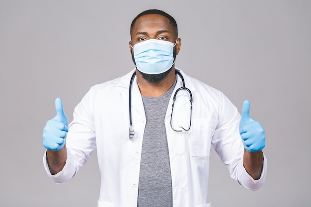 Afroamerikanischer arzt, der medizinische maske und handschuhe trägt. daumen hoch.