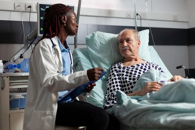 Afroamerikanischer arzt liest diagnose aus der zwischenablage