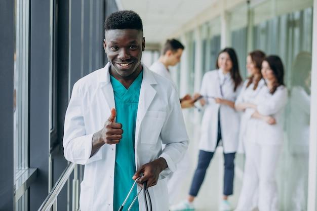 Afroamerikanischer arzt mann mit daumen hoch, im korridor des krankenhauses stehend
