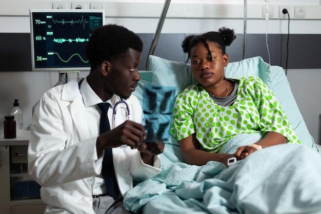 Afroamerikanischer arzt und patient, der röntgenstrahlen betrachtet