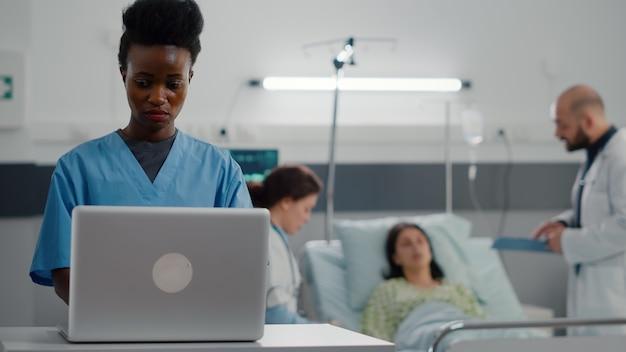 Afroamerikanischer assistent, der krankheitssymptome auf dem computer eingibt