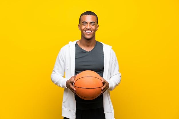 Afroamerikanischer basketball-spielermann über getrenntem gelb