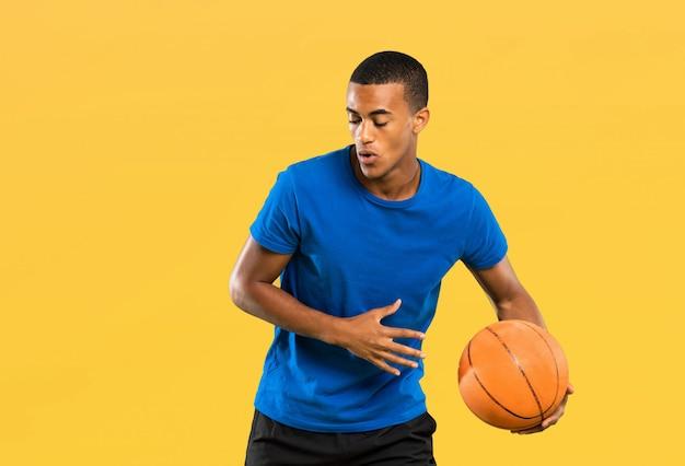 Afroamerikanischer basketball-spielermann über lokalisierter gelber wand