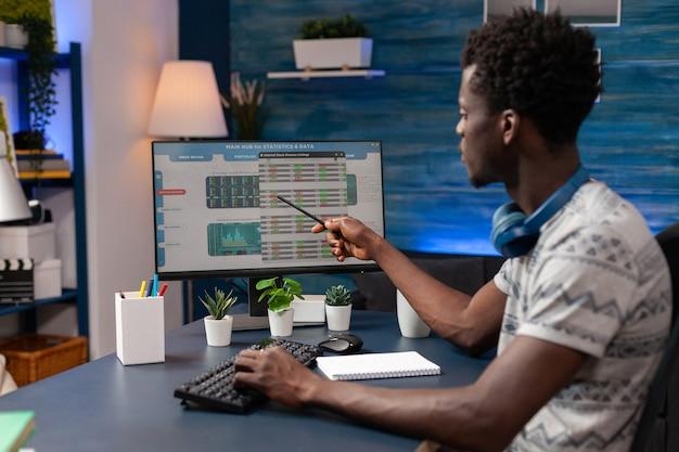 Afroamerikanischer borker, der auf digitale krypto-investitionen zeigt