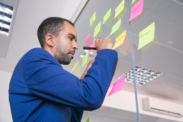 Afroamerikanischer büroarbeitgeber, der auf aufkleber mit markierung schreibt. konzentrierter, selbstbewusster geschäftsmann in der anzug-sharing-idee für das projekt und das notieren