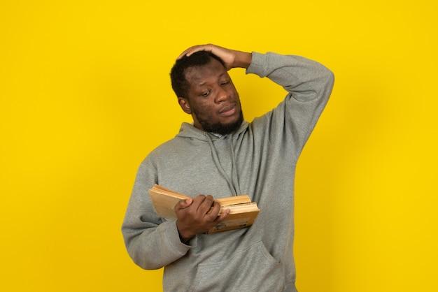 Afroamerikanischer denkender mann, der bücher in seiner hand liest, steht über gelber wand.