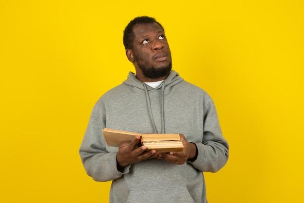 Afroamerikanischer denkender mann, der interessante bücher in seiner hand liest, steht über gelber wand.