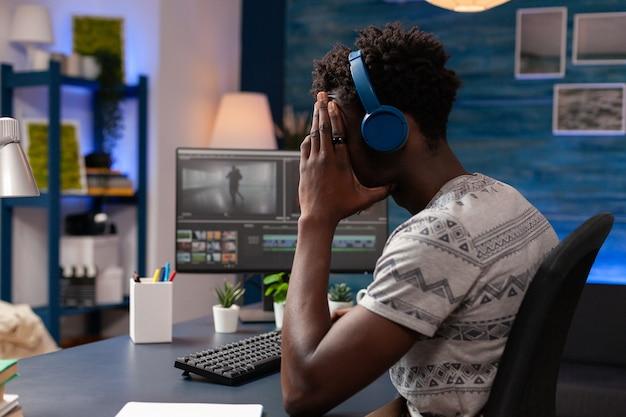 Afroamerikanischer editor retuschiert filmmontage mit der postproduktionssoftware zur bearbeitung