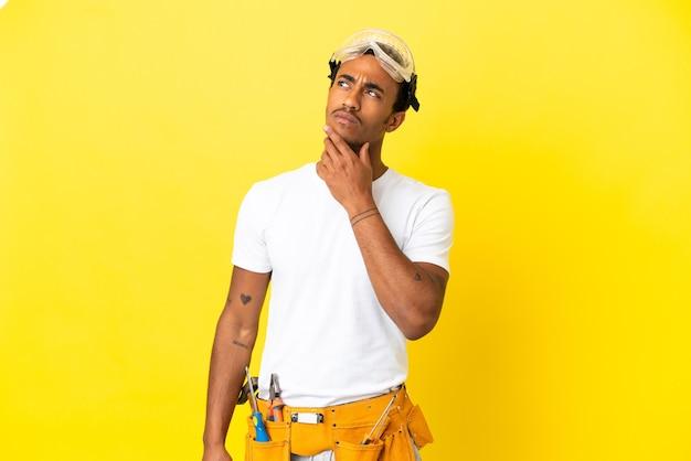 Afroamerikanischer elektrikermann über isolierter gelber wand, der beim nachschlagen zweifel hat