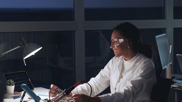 Afroamerikanischer elektronikspezialist für schutzbrillen und weißen kittel, der mit multimetertester und motherboard im labor arbeitet