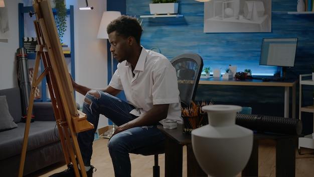 Afroamerikanischer erwachsener, der im kunstwerkstudio sitzende kunst macht