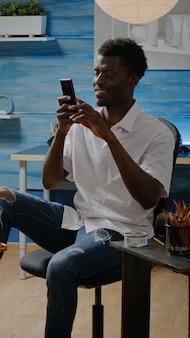 Afroamerikanischer erwachsener, der smartphone für den zeichenprozess verwendet
