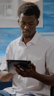 Afroamerikanischer erwachsener mit künstlerischen fähigkeiten mit digitalem tablet zum zeichnen von design im kunstwerkraum zu hause. schwarzer junger künstler, der an leinwand und staffelei für meisterwerke mit technologie arbeitet