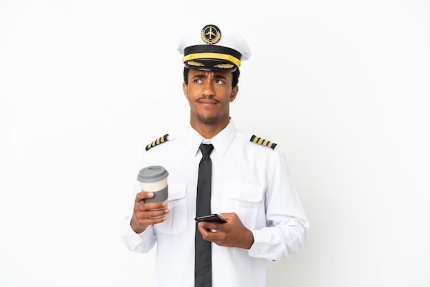 Afroamerikanischer flugzeugpilot über isoliertem weißem hintergrund, der kaffee zum mitnehmen und ein handy hält, während er etwas denkt